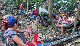 In this photo released by the Free Burma Rangers, Karen villagers gather in the forests as they hide from military airstrikes in the Deh Bu Noh area of the Papun district, north Karen state, Myanmar, Sunday, March 28, 2021. Thai authorities along its northwestern border braced themselves, Monday, for a possible influx of more ethnic Karen villagers fleeing the fear of renewed air strikes from the Myanmar military. (Free Burma Rangers via AP)