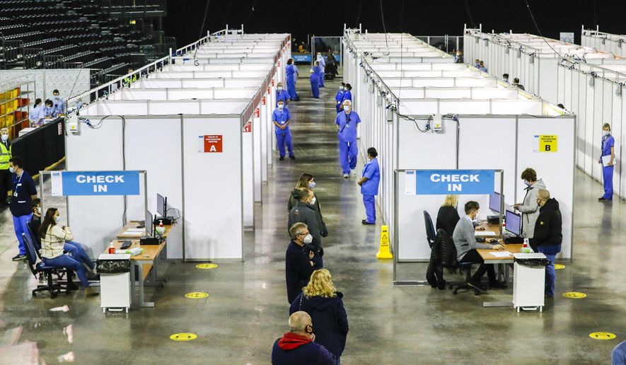 People queue to receive the coronavirus vaccine at the newly opened Covid-19 vaccination centre in the SSE Arena, Belfast, Northern Ireland, Monday March 29, 2021.  The vaccination program continues to increase in an effort to control the spread of COVID-19 virus.(Liam McBurney/PA via AP)