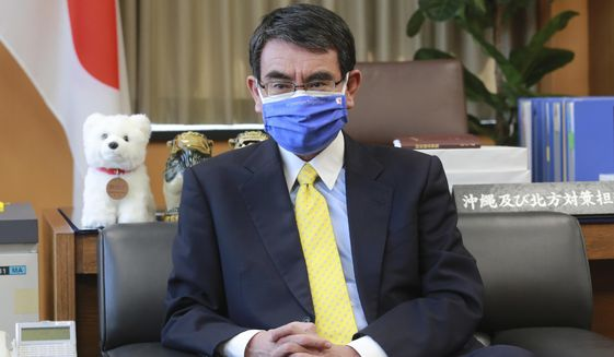Japanese Vaccine Minister Taro Kono wearing a face mask with Japanese and EU flags on it speaks during an interview in Tokyo, Monday, March 29, 2021. Kono tasked with COVID-19 vaccinations urged the EU to ensure stable shipment of Pfizer vaccines amid distribution uncertainty in a country where the Olympics are coming up in four months. (AP Photo/Koji Sasahara)