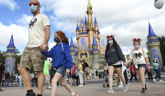 In this Dec. 21, 2020, file photo, a family walks past Cinderella Castle in the Magic Kingdom, at Walt Disney World in Lake Buena Vista, Fla. (Joe Burbank/Orlando Sentinel via AP, File)
