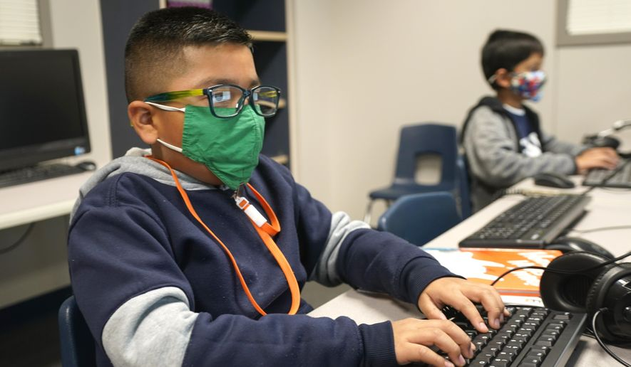 In this Dec. 3, 2020, file photo, students wearing face masks work on computers at Tibbals Elementary School in Murphy, Texas. A new poll from The University of Chicago Harris School of Public Policy and The Associated Press-NORC Center for Public Affairs Research finds that most parents fear that their children are falling behind in school while at home during the pandemic (AP Photo/LM Otero, File)
