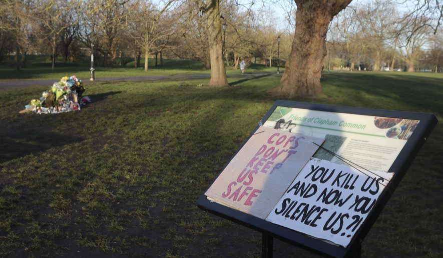 Placards and floral tributes are placed near the bandstand in Clapham Common on Sunday, March 14, 2021, in memory of Sarah Everard who was abducted and murdered after last being seen walking home from a friend's apartment in south London on the night of March 3. Hundreds of people in London defied coronavirus restrictions Saturday to pay their respects to Everard who disappeared while walking home and was found dead a week later. (AP Photo/Tony Hicks)
