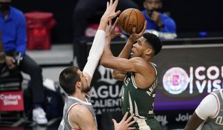Milwaukee Bucks forward Giannis Antetokounmpo, right, shoots as Los Angeles Clippers center Ivica Zubac defends during the first half of an NBA basketball game Monday, March 29, 2021, in Los Angeles. (AP Photo/Mark J. Terrill)