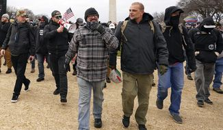 In this Jan. 6, 2021, photo, Proud Boys including Joseph Biggs, front left, walks toward the U.S. Capitol in Washington, in support of President Donald Trump. With the megaphone is Ethan Nordean, second from left. The Proud Boys and Oath Keepers make up a fraction of the more than 300 Trump supporters charged so far in the siege that led to Trump's second impeachment and resulted in the deaths of five people, including a police officer. But several of their leaders, members and associates have become the central targets of the Justice Department's sprawling investigation. (AP Photo/Carolyn Kaster) **FILE**