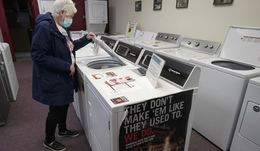 Alanna Kelly, of Norwood, Mass., examines clothes washers and dryers on display at Sam's Appliances TV & Furniture, Thursday, March 25, 2021, in Norwood.  U.S. consumer confidence surged in March to the highest reading in a year, helped by increased vaccinations and more government economic support. The Conference Board said Tuesday, March 30, its consumer confidence index rose to 109.7 in March, the best showing since it stood at 118.8 in March of last year as the pandemic was beginning to hit the United States.   (AP Photo/Steven Senne)
