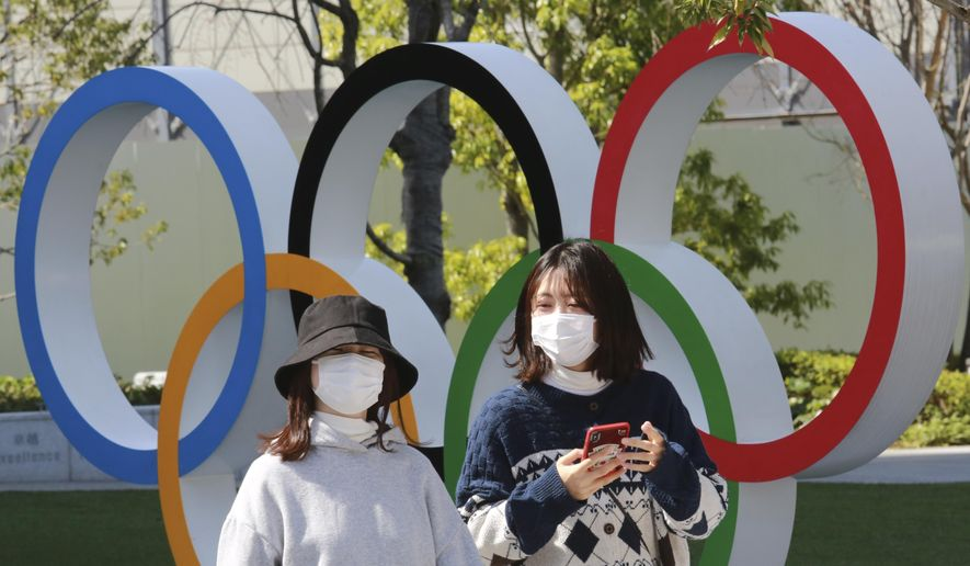 FILE - In this March 17, 2021, file photo, people walk past the Olympic rings in Tokyo. The Tokyo Olympics open in under four months, and the torch relay has begun to crisscross Japan with 10,000 runners. Organizers say they are mitigating the risks, but many medial expert aren't convinced.(AP Photo/Koji Sasahara)
