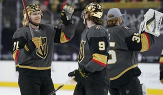 Vegas Golden Knights center William Karlsson (71) and center Cody Glass (9) celebrate after defeating the Los Angeles Kings in an NHL hockey game Monday, March 29, 2021, in Las Vegas. (AP Photo/John Locher)