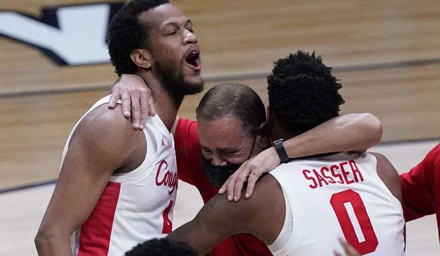 Houston forward Justin Gorham, left, head coach Kelvin Sampson and Marcus Sasser (0) celebrate after beating Oregon State during an Elite 8 game in the NCAA men's college basketball tournament at Lucas Oil Stadium, Monday, March 29, 2021, in Indianapolis. Houston won 67-61. (AP Photo/Darron Cummings)