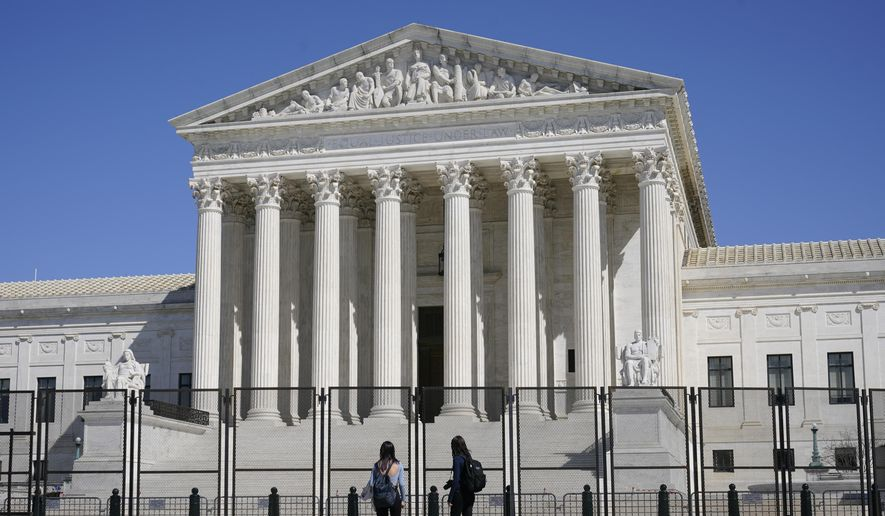 In this March 21, 2021, file photo people view the Supreme Court building from behind security fencing on Capitol Hill in Washington after portions of an outer perimeter of fencing were removed overnight to allow public access. A Supreme Court case being argued this week amid March Madness could erode the difference between elite college athletes and professional sports stars. (AP Photo/Patrick Semansky, File)