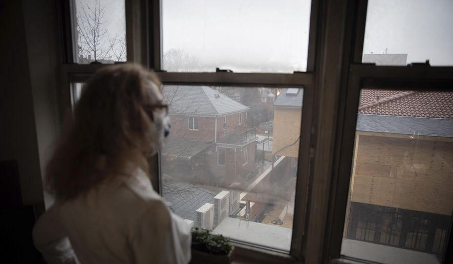 Bonney Ginett gazes out the window of her apartment in the Queens borough of New York on Thursday, March 18, 2021. Ginett, whose massage therapy business dried up during the pandemic, applied for help in July and said she was denied in October because she failed to prove loss of income. The 65-year-old New York City resident now owes more than $26,000 in back rent on her one-bedroom apartment and fears eviction. (AP Photo/Robert Bumsted) ** FILE **