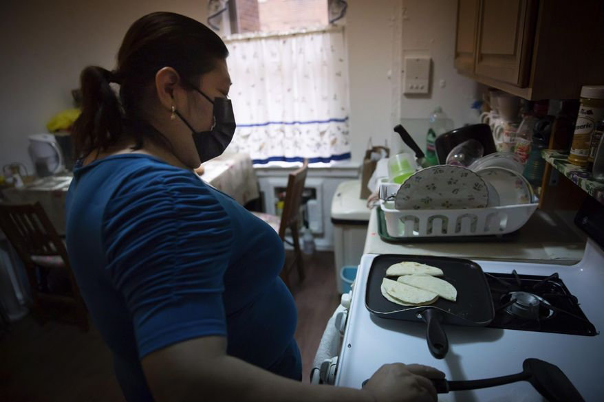 Candida Uraga prepares a meal in the kitchen of her apartment in New York on Friday, March 19, 2021. She has struggled to pay rent after being laid off from her job as a teaching assistant during the pandemic and was denied help under a federally-funded rental assistance program. (AP Photo/Robert Bumsted) ** FILE **