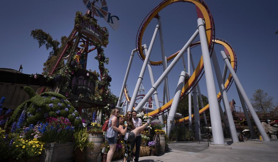 Visitors pose for photos during the Knott's Taste of Boysenberry Festival at Knott's Berry Farm in Buena Park, Calif., Tuesday, March 30, 2021. Massive Los Angeles County can reopen even more businesses, California public health officials announced Tuesday. The county of 10 million people was one of several counties, including neighboring Orange County, that moved into the state's second-least restrictive orange tier amid low coronavirus case rates. (AP Photo/Jae C. Hong)