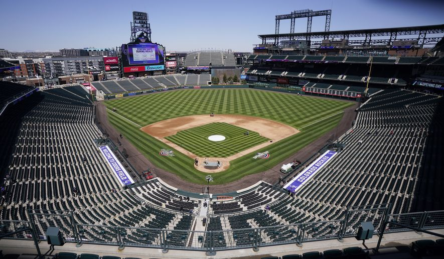 Workers prepare Coors Field on Wednesday, March 31, 2021, in Denver, the day before the Colorado Rockies' season-opener against the Los Angeles Dodgers. (AP Photo/David Zalubowski) **FILE**
