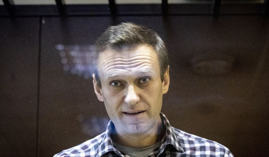 In this photo taken on Saturday, Feb. 20, 2021, Russian opposition leader Alexei Navalny looks at photographers standing behind a glass of the cage in the Babuskinsky District Court in Moscow, Russia. Alexei Navalny says on Wednesday, March 31 he has started a prison hunger strike to protest officials' failure to provide proper treatment for his back and leg pains. He also protested the hourly checks a guard makes on him at night, saying they amount to sleep deprivation torture. (AP Photo/Alexander Zemlianichenko)