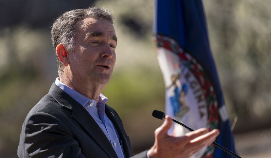In this March 30, 2021, file photo, Virginia Gov. Ralph Northam speaks at a news conference to announce the expansion of commuter rail in Virginia at the Amtrak and Virginia Railway Express (VRE) Alexandria Station, in Alexandria, Va. (AP Photo/Andrew Harnik, File)
