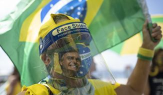 A woman wearing a face shield and mask decorated with an image of Brazilian President Jair Bolsonaro takes part in a demonstration to show support for Bolsonaro, after leaders of all three branches of the armed forces jointly resigned following the president's replacement of the defense minister, on Copacabana beach in Rio de Janeiro, Brazil, Wednesday, March 31, 2021. (AP Photo/Silvia Izquierdo)