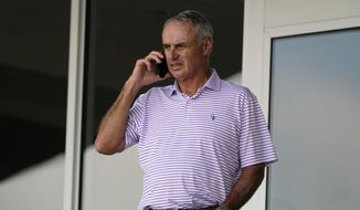 Major League Baseball Commissioner Rob Manfred speaks on his phone as he watches a spring training baseball game between the Atlanta Braves and Boston Red Sox on Wednesday, March 10, 2021, in Fort Myers, Fla. (AP Photo/John Bazemore)