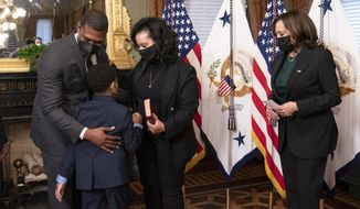 Vice President Kamala Harris, right, watches EPA administrator Michael Regan gives his wife Melvina Thomas Regan and son Matthew Silas, 7 a hug, during a ceremonial swearing-in ceremony in the Vice President's Ceremonial Office at the Eisenhower Executive Office Building on the White House complex in Washington, Wednesday, March 17, 2021. (AP Photo/Manuel Balce Ceneta)