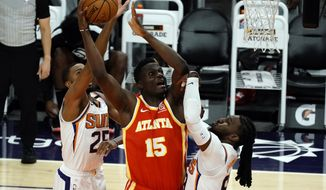 Atlanta Hawks center Clint Capela (15) shoots over Phoenix Suns forward Mikal Bridges (25) and forward Jae Crowder (99) during the first half of an NBA basketball game Tuesday, March 30, 2021, in Phoenix. (AP Photo/Rick Scuteri)