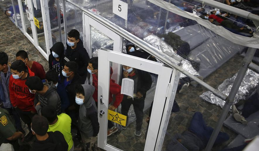 Young minors talk to an agent outside at a pod in the Donna Department of Homeland Security holding facility, the main detention center for unaccompanied children in the Rio Grande Valley run by the U.S. Customs and Border Protection (CBP), in Donna, Texas, Tuesday, March 30, 2021. The minors are housed by the hundreds in eight pods that are about 3,200 square feet in size. Many of the pods had more than 500 children in them. The Biden administration on Tuesday for the first time allowed journalists inside its main detention facility at the border for migrant children, revealing a severely overcrowded tent structure where more than 4,000 kids and families were crammed into pods and the youngest kept in a large play pen with mats on the floor for sleeping. (AP Photo/Dario Lopez-Mills, Pool)