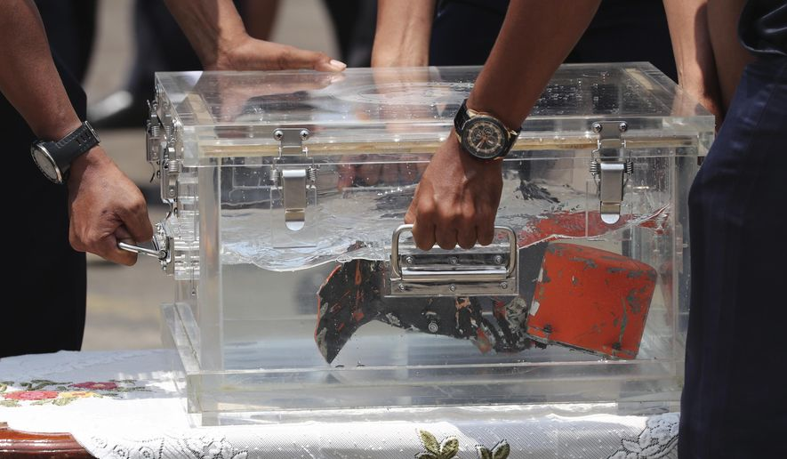 National Transportation Safety Committee investigators carry a box containing the cockpit voice recorder of Sriwijaya Air flight SJ-182 retrieved from the waters off Java Island where the passenger jet crashed in January, during a press conference at Tanjung Priok Port in Jakarta, Indonesia, Wednesday, March 31, 2021. (AP Photo/Tatan Syuflana)