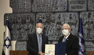 Chairman of Israel's Central Elections Committee Judge Uzi Fogelman, left, poses with Israeli President Reuvin Rivlin with official election results in Jerusalem, Wednesday, March 31, 2021. Israeli election officials Wednesday handed the results of last week's vote to President Reuven Rivlin, nudging forward the country' elusive efforts to break political deadlock, form a government and avoid an unprecedented fifth consecutive round of balloting.  (AP Photo/Maya Alleruzzo)