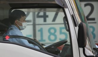 A car stops in front of an electronic stock board of a securities firm in Tokyo, Wednesday, March 31, 2021. Asian shares were mixed Wednesday as data showed a strong economic recovery in China but worries lingered about the coronavirus pandemic. (AP Photo/Koji Sasahara)
