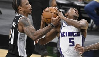 San Antonio Spurs' DeMar DeRozan, left, strips the ball from Sacramento Kings' De'Aaron Fox during the second half of an NBA basketball game Wednesday, March 31, 2021, in San Antonio. (AP Photo/Darren Abate)