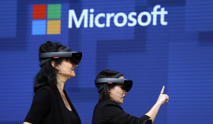 In this May 11, 2017, file photo, members of a design team at Cirque du Soleil demonstrate use of Microsoft's HoloLens device in helping to virtually design a set at the Microsoft Build 2017 developers conference in Seattle. Microsoft says it has won a nearly $22 billion contract to supply U.S. Army combat troops with its virtual reality headsets. Microsoft announced the deal Wednesday, March 31, 2021. (AP Photo/Elaine Thompson, File)