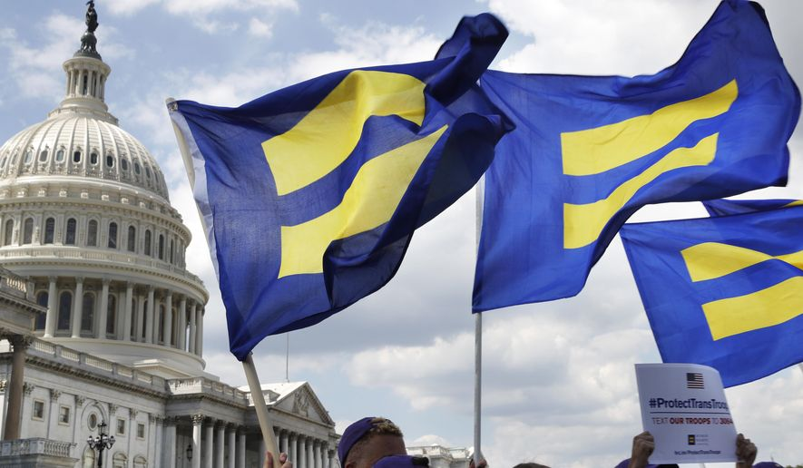 """In this July 26, 2017 file photo, people with the Human Rights Campaign hold up """"equality flags"""" during an event on Capitol Hill in Washington, in support of transgender members of the military. Defense officials say the Pentagon will sweep away Trump-era policies that largely banned transgender people from serving in the military and will issue new rules that broaden their access to medical care and gender transition. (AP Photo/Jacquelyn Martin, File)"""