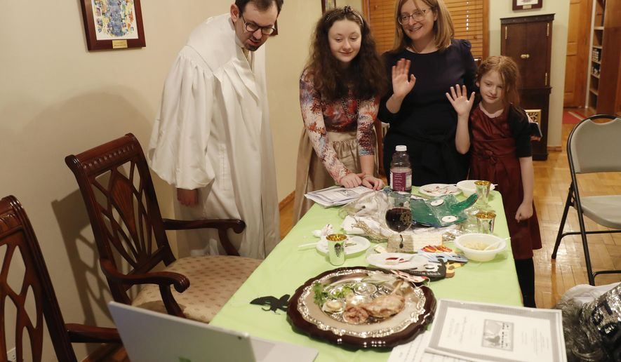 In this Wednesday, April 8, 2020, file photo, Rabbi Shlomo Segal, left, and his family wave goodbye to participants after he conducted a virtual Passover seder for members of his congregation, friends and family broadcast on YouTube from his home in the Sheepshead Bay neighborhood of Brooklyn during the current coronavirus outbreak in New York. From left, are Segal; daughter Shira, 12; wife, Adina, and daughter, Rayna, 8. In 2021, the Sabbath led directly into Passover, limiting the use of technology for Segal and his congregants. Instead of streaming their seder, the synagogue provided online workshops prior to Passover so families could do it on their own. Segal says that many of his members are still reluctant to gather together in person. (AP Photo/Kathy Willens)