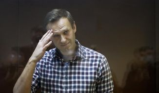 In this Saturday, Feb. 20, 2021, file photo, Russian opposition leader Alexei Navalny stands in a cage in the Babuskinsky District Court in Moscow, Russia. Russian opposition leader Alexei Navalny says he has started a prison hunger strike to protest officials' failure to provide proper treatment for his back and leg pains. (AP Photo/Alexander Zemlianichenko, File)