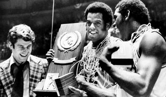 FILE - In this March, 1976, file photo, Indiana coach Bobby Knight, left, and team members Scott May, center, and Quinn Buckner, right, celebrate with the trophy after winning the NCAA Basketball Championship in Philadelphia in this Monday, March 30, 1976, file photo. They beat Michigan 86-68. The Indiana Hoosiers sat quietly inside their locker room on March 22, 1975. They knew what the first and only loss that season signified — one perfect quest ended while another began. Minutes after losing 92-90 to archrival Kentucky in the Mideast Regional championship, the underclassmen vowed to come back the next season and go undefeated. They did. And 45 years later, the 1975-76 Hoosiers remain America's last perfect college basketball team.  (AP Photo/File)