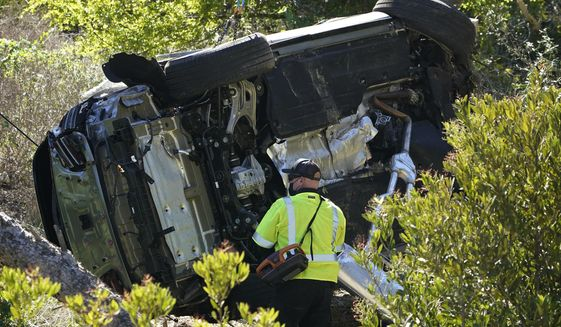 FILE - In this Feb. 23, 2021, file photo a vehicle rests on its side after a rollover accident involving golfer Tiger Woods, in Rancho Palos Verdes, Calif., a suburb of Los Angeles. The Los Angeles County sheriff says detectives have determined what caused Tiger Woods to crash his SUV last month in Southern California but would not release details on Wednesday, March 31, 2021, citing privacy concerns for the golf star. (AP Photo/Marcio Jose Sanchez, File)