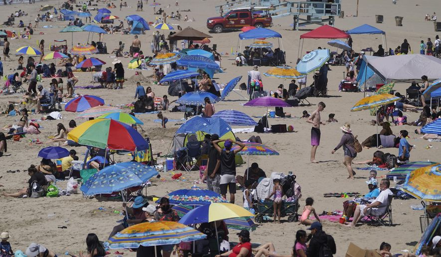 People enjoy the hot weather on Santa Monica Beach in Santa Monica, Calif., Wednesday, March 31, 2021. Half of the state's nearly 40 million people are now in the state's second-least restrictive orange tier amid low coronavirus case rates and increased vaccinations. Health officials in California and across the country are urging caution because of a troubling rise in new cases of COVID-19.  (AP Photo/Damian Dovarganes)