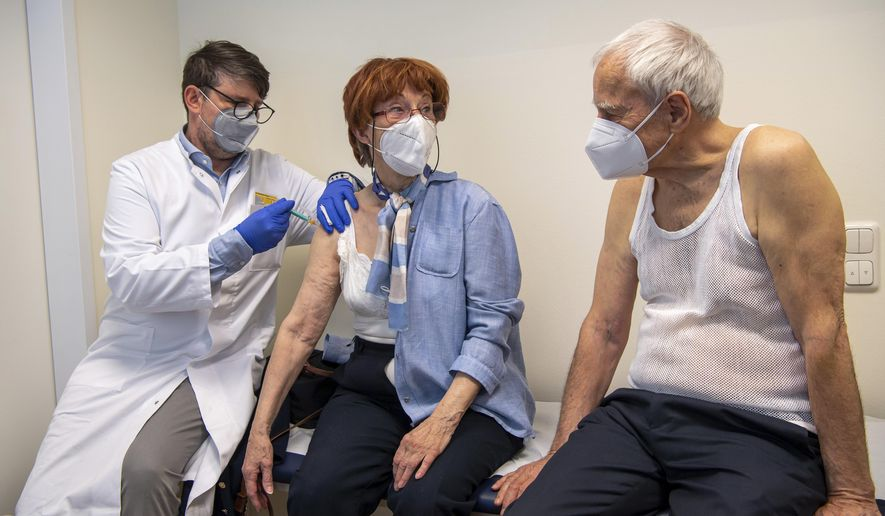 The doctor Wolfgang Ritter vaccinates the couple Edith and Erich Dengler at the start of the Corona vaccinations in Bavarian GP practices in Munich, Germany, Wednesday, March 31, 2021. Vaccinated was the vaccine from Astrazeneca. (Peter Kneffel/dpa via AP)
