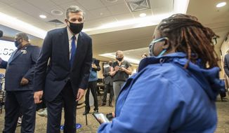 Gov. Roy Cooper, left, asks a patient how her vaccine went at CaroMont Health in Gastonia, N.C., on Wednesday, March 31, 2021. (Khadejeh Nikouyeh/The News & Observer via AP)