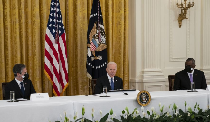 Secretary of State Antony Blinken, left, and Secretary of Defense Lloyd Austin listen as President Joe Biden speaks during a Cabinet meeting in the East Room of the White House, Thursday, April 1, 2021, in Washington. (AP Photo/Evan Vucci)