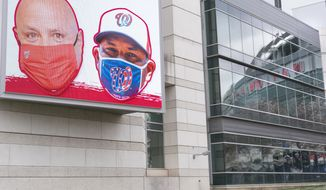 An electronic sign encouraging mask wearing is seen at Nationals Park, after the opening day game was cancelled due to COVID-19, Thursday, April 1, 2021, in Washington. (AP Photo/Jacquelyn Martin)