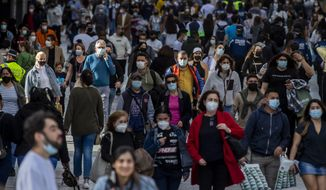 """People wearing face masks to protect against the spread of coronavirus walk in downtown Madrid, Spain, Wednesday, March 31, 2021. Spain is bracing for another potential sharp increase in coronavirus cases. And with the vaccine rollout being outpaced by the new more contagious variant of the virus, authorities are asking for citizens to intensify their precautions to """"buy time"""" for the shots to arrive. (AP Photo/Manu Fernandez)"""