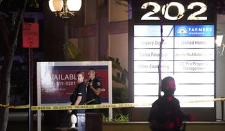 Police officers stand outside a business building where a shooting occurred in Orange, Calif., Wednesday, March 31, 2021. Police say several people were killed, including a child, and the suspected shooter was wounded by police. (AP Photo/Jae C. Hong)