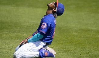 New York Mets shortstop Francisco Lindor reacts after he can't get to a ball hit for a single by St. Louis Cardinals' Yadier Molina during the third inning of a spring training baseball game, Sunday, March 14, 2021, in Port St. Lucie, Fla. (AP Photo/Lynne Sladky)