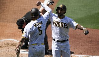 San Diego Padres' Eric Hosmer, right, is congratulated by teammate Wil Myers after hitting a solo home run during the third inning of a baseball game against the Arizona Diamondbacks, Thursday, April 1, 2021, on opening day in San Diego. (AP Photo/Denis Poroy)