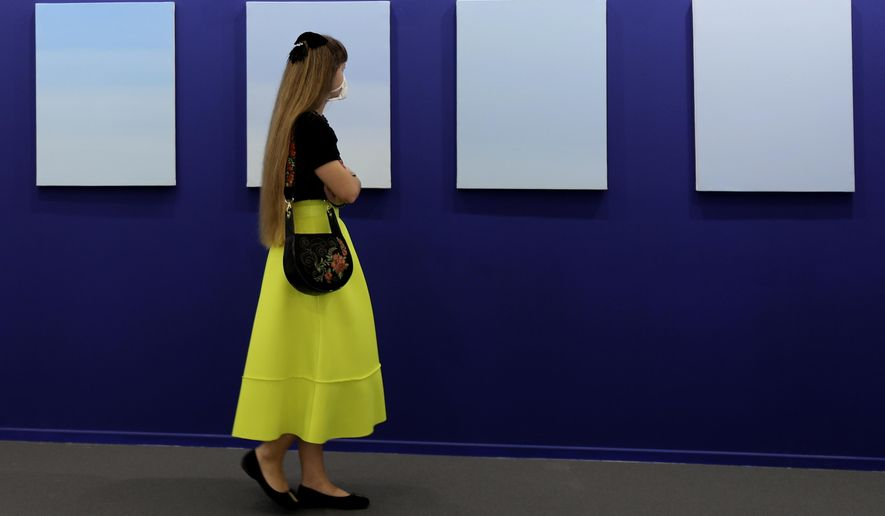 A woman visits oil on canvas paintings by Ayesha Sultana of the Experimenter gallery in 14th edition of Art Dubai at Dubai International Financial Centre, DIFC, which features 50 galleries from 31 countries with a focus on modern and contemporary art, in Dubai, United Arab Emirates, Tuesday, March 30, 2021. (AP Photo/Kamran Jebreili)