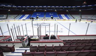 Off-ice officials pack up equipment after the Vancouver Canucks and Calgary Flames NHL hockey game was postponed due to a positive COVID-19 test result in Vancouver, British Columbia, Wednesday, March 31, 2021. (Darryl Dyck/The Canadian Press via AP)