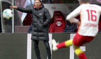 Leipzig's head coach Julian Nagelsmann points as Leipzig's Lukas Klostermann shoots the ball during the German Bundesliga soccer match between RB Leipzig and Eintracht Frankfurt in Leipzig, Germany, Sunday, March 14, 2021. (AP Photo/Michael Sohn)