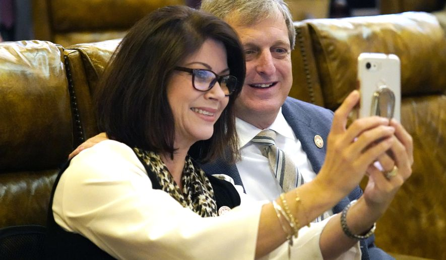 """Republican Reps. Carolyn Crawford of Pass Christian, left, and Donnie Scoggin of Ellisville, smile for a """"selfie"""" photograph during a recess in the House, Wednesday, March 31, 2021 at the the Capitol in Jackson, Miss. Lawmakers in both chambers worked steadily to meet deadlines on the remaining legislation to be completed this session and are expected to Sine Die on Thursday. (AP Photo/Rogelio V. Solis)"""