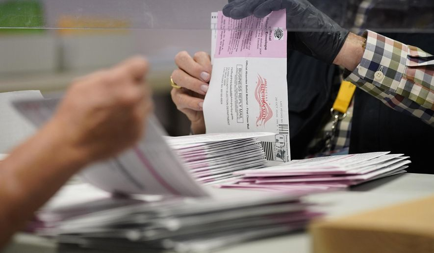 In this a Clark County election department facility Oct. 31, 2020, file photo, County employees process mail-in ballots in Las Vegas. Nevada lawmakers are considering sending mail-in ballots to all active voters in future elections after passing a law last summer that directed election officials to do so to prevent the coronavirus from spreading at polling places. A legislative committee is scheduled on Thursday, April 1, 2021, to hear a proposal to make the policy permanent. (AP Photo/John Locher, File)