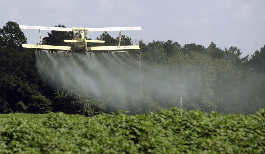 FILE - In this Aug. 4, 2009 file photo, a crop duster sprays a field in Alabama. A study published in the journal Science on Thursday, April 1, 2021 finds that farmers in the U.S. are using smaller amounts of better targeted pesticides, but these are harming pollinators, aquatic insects and some plants far more than decades ago. (AP Photo/Dave Martin, File)