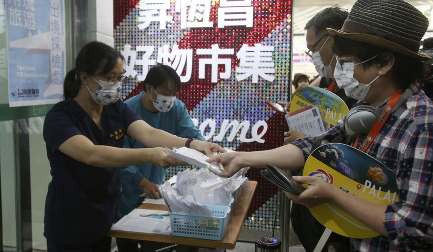 Taiwanese travelers, right, of the first group of Palau-Taiwan Travel Corridor prepare to take COVID-19 virus antigen test before leaving Taiwan, at Taoyuan International Airport in Taoyuan, northern Taiwan, Thursday, April 1, 2021. The Palau-Taiwan Travel Corridor, allowing people to travel between the islands without a COVID-19 quarantine, has started Thursday. (AP Photo/Chiang Ying-ying)